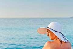 Portrait of a young woman in a white hat on a background of the sea Royalty Free Stock Image