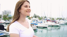 Portrait of young woman standing alone on pier. Wind from sea blowing female hair in slow motion stock video footage