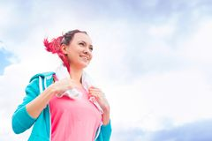 Portrait of young woman with white towel in sportswear resting after workout or training over sky.  Royalty Free Stock Image
