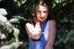 Portrait of a young woman who poses on the background spruce Stock Photo