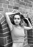 Portrait of a young woman. Portrait of a young woman who is posing at a brick wall.  Black and white Stock Photo