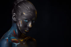 Portrait of a young woman who is posing covered with  black paint Royalty Free Stock Image