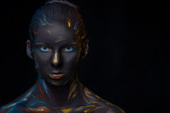 Portrait of a young woman who is posing covered with  black paint Stock Photography