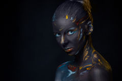 Portrait of a young woman who is posing covered with  black paint Stock Photos