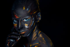 Portrait of a young woman who is posing covered with  black paint Royalty Free Stock Photos