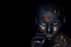 Portrait of a young woman who is posing covered with  black paint Stock Images