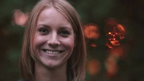 Portrait of young woman who standing at the park in the rays of the setting sun, looking to camera and smiling, close-up