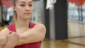 Portrait of young woman, who is warming up her muscules before training in modern gym, slow motion. Beautiful blond lady in red sportswear is standing in big stock footage