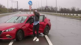 Portrait of a young woman who was in a car accident in bad weather. Portrait of a young woman who was in a car accident in bad weather, she is standing near a stock footage