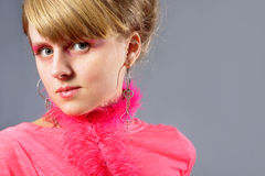 Portrait of young woman wich pink plume. Portrait of young woman with pink plume over gray background. Woman with pink make-up Stock Image