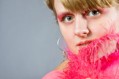 Portrait of young woman wich pink plume. Portrait of young woman with pink plume over gray background. Woman with pink make-up Stock Images
