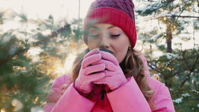Portrait of a young woman in winter forest. Drinks from a cup of hot tea stock video footage