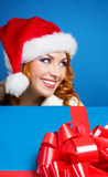 Portrait of a young woman in a winter hat holding a present Royalty Free Stock Photo