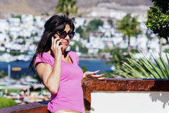 Portrait of  young woman wondering while  talking on the phone Stock Photo