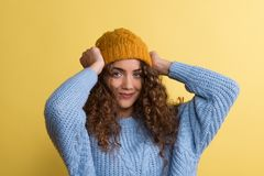 Portrait of a young woman with woolen hat in a studio on a yellow background. Portrait of a young woman with woolen hat and sweater in a studio on a yellow stock images