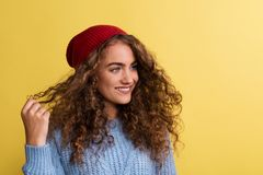 Portrait of a young woman with woolen hat in a studio on a yellow background. Portrait of a young woman with woolen hat and sweater in a studio on a yellow royalty free stock photography