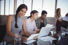 Portrait of young woman working with colleagues at creative office desk. Portrait of smiling young women working with colleagues at creative office desk Royalty Free Stock Images