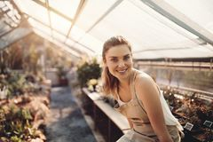Beautiful woman working in greenhouse. Portrait of young woman working in greenhouse. Beautiful gardener sitting at plant nursery Royalty Free Stock Photography