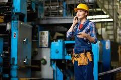 Female Worker Speaking by Phone in Factory Workshop Stock Photo
