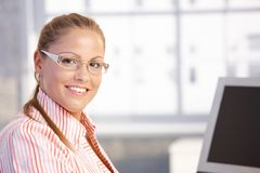 Portrait of young woman working in office smiling. Portrait of young woman sitting at desk, working with computer, smiling royalty free stock photography