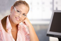 Portrait of young woman working in office smiling. Portrait of young woman sitting at desk, working with computer, smiling stock image