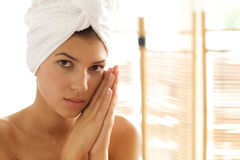 Portrait of young woman wrapped in towel with hands clasped Royalty Free Stock Images