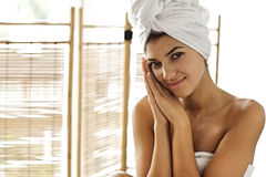 Portrait of young woman wrapped in towel with hands clasped Stock Photo