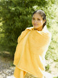 Portrait of a young woman wrapped in a towel and smiling royalty free stock image