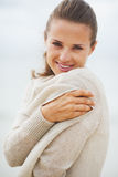 Portrait of young woman wrapping in sweater on coldly beach Stock Photos