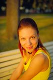 Portrait of young woman in yellow dress, sitting in a summer park on a bench Royalty Free Stock Images
