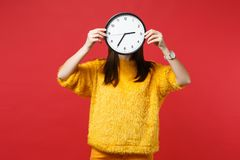 Portrait of young woman in yellow fur sweater hiding, covering face, holding round clock isolated on bright red. Background in studio. People sincere emotions royalty free stock image