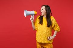Portrait of young woman in yellow fur sweater looking aside, screaming on megaphone isolated on bright red wall. Background in studio. People sincere emotions royalty free stock photo