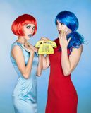 Portrait of young women in comic pop art make-up style. Females. In red and blue wigs and dresses call on the phone Stock Photos