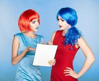 Portrait of young women in comic pop art make-up style. Females. In red and blue wigs and dresses are reading letter Royalty Free Stock Photo