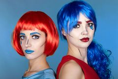 Portrait of young women in comic pop art make-up style. Females. In red and blue wigs on blue background stock image
