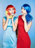 Portrait of young women in comic pop art make-up style. Females. In red and blue wigs and dresses call on the phone Royalty Free Stock Photos