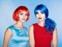 Portrait of young women in comic pop art make-up style. Females. In red and blue wigs and dresses Royalty Free Stock Images