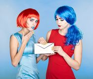 Portrait of young women in comic pop art make-up style. Females. In red and blue wigs and dresses are reading letter Royalty Free Stock Image