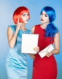 Portrait of young women in comic pop art make-up style. Females. In red and blue wigs and dresses are reading letter Stock Image