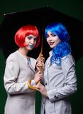 Portrait of young women in comic pop art make-up style. Females. With umbrella on dark background Royalty Free Stock Photography