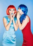 Portrait of young women in comic pop art make-up style. Shocked. Females in red and blue wigs and dresses Stock Photography