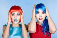 Portrait of young women in comic pop art make-up style. Shocked. Females in red and blue wigs and dresses Stock Photos