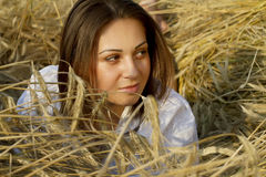 Portrait of a young women on a field. Portrait of a young brown-haired woman lying on a field of wheat ears Stock Image
