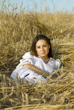 Portrait of a young women on a field. Portrait of a young brown-haired woman lying on a field of wheat ears in national dress Royalty Free Stock Images