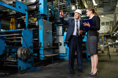 Senior Investor Touring Factory. Portrait of young women giving a tour of modern factory to senior businessman  wearing hardhat Royalty Free Stock Image