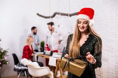 Portrait of a young woman with a gold giftbox at home on the foreground. Beautiful blonde in a Santa hat and black dress Stock Images
