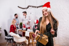 Portrait of a young woman with a gold giftbox at home on the foreground. Beautiful blonde in a Santa hat and black dress Stock Photography