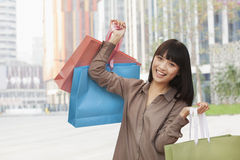 Portrait of young women holding shopping bags outdoors, Beijing Stock Images