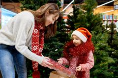 Young Family Buying Christmas Decorations. Portrait of young women with little girl buying Christmas decorations in mall, packing colorful ornaments into paper Stock Photography