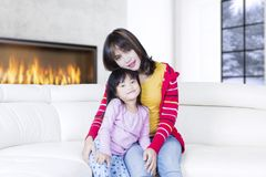Young woman and little girl sit together Royalty Free Stock Image